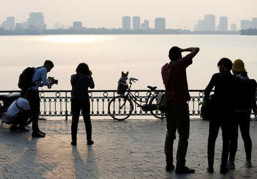 People photograph a dog by the Westlake after the government eased the nationwide lockdown during the coronavirus disease (COVID-19) outbreak in Hanoi