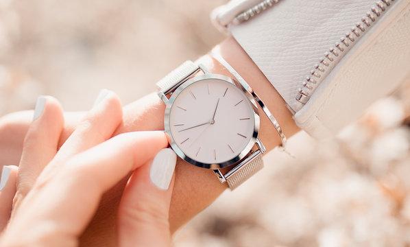 Beautiful elegant white watch on woman hand. Close-up photo.