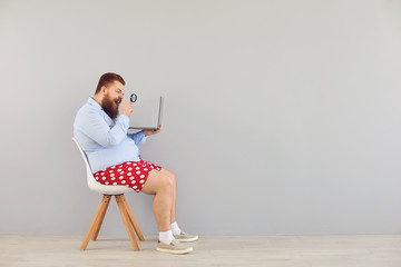 Funny man in red shorts with a laptop increases magnifying information on a gray background....