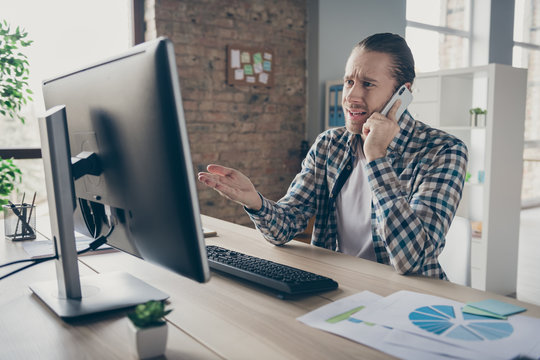 Photo of business administrator guy pointing hand computer monitor table speak telephone client internet service terrible connection speed wear casual shirt sit modern office indoors