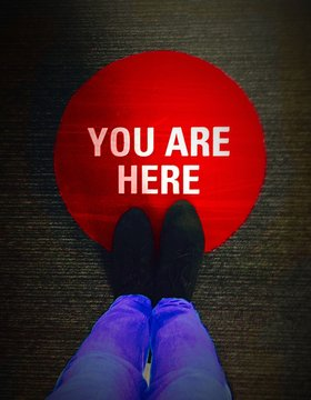 Low Section Of Person Standing On You Are Here Sign