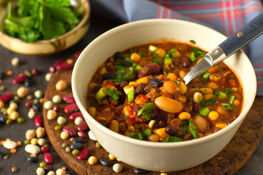 Cooked mixed legumes beans lentils stew with tomatoes , vegan comfort food