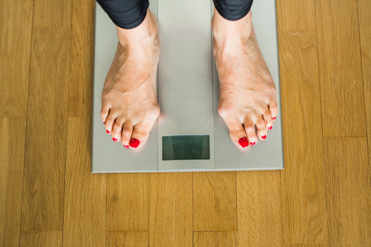 legs of an adult woman on electronic scales