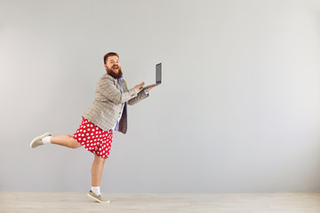 Fototapeta Funny fat man in a jacket works using a laptop while dancing on a gray background.