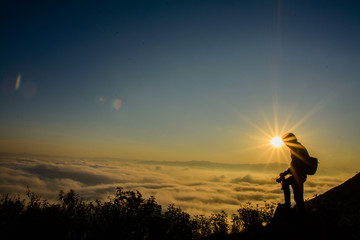 photographer stand at the top of the mountain, under the sunset and he is higher than the sun