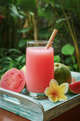 Wall Mural - Guava smoothie in glass with bamboo drinking straw