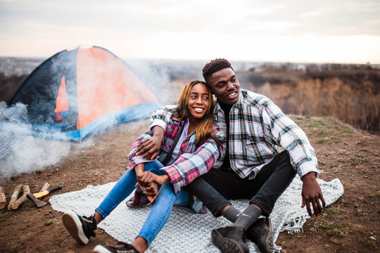 African American man and woman sitting on rug near campfire and tent, smiling, hugging each other. Man and woman in shirt.