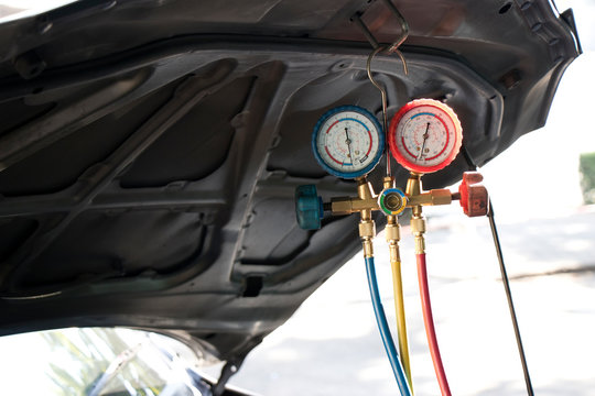 Pressure gauges with colorful pressure hose for car air condition system hanging under hood.
