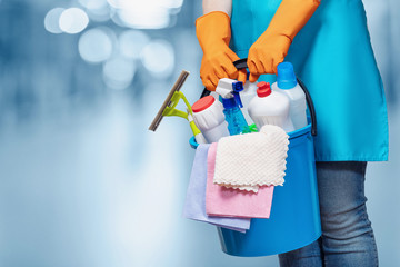 A cleaning lady is holding a bucket of cleaning products on a blurred background.