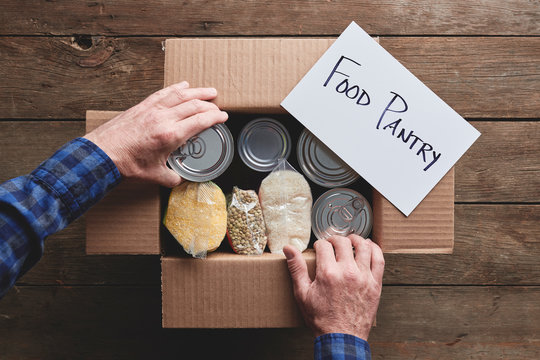 a person packing a donation box with food items for a food pantry delivery