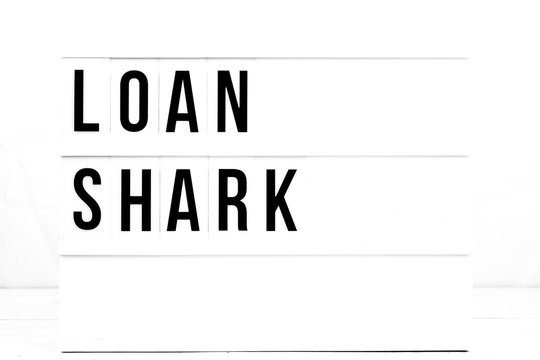 Loan Shark Warning sign on Vintage Retro Board. Business Flat Lay
