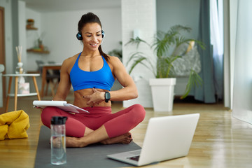 Happy personal trainer holding online exercise class with her clients from home.