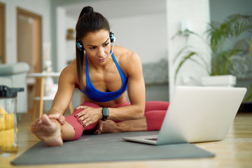 Young sportswoman stretching on the floor while using laptop at home.