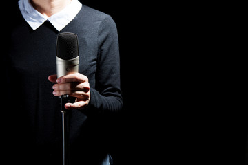 Female singer on the stage holding a microphone on a dark background