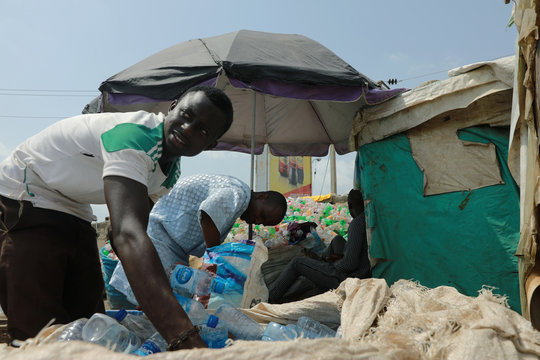 Two men sort recycled empty bottles, as authorities race to contain the spread of coronavirus disease (COVID-19) in Abuja