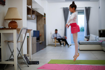 Michela Perrini, 9, practices ballet in her living room using a video tutorial on her laptop in the small southern historical town of Cisternino