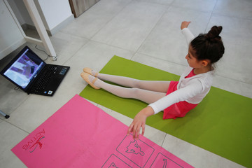 Michela Perrini, 9, practices ballet in her living room using a video tutorial on her laptop, in the small southern historical town of Cisternino