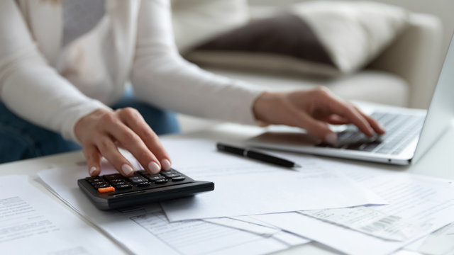 Close up of woman busy paying bills online on computer calculating household finances or taxes on machine, female manage home family expenditures, using calculator, make payment on laptop