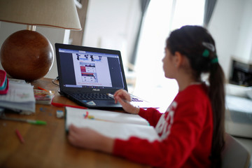 Michela Perrini, 9, studies in her living room using her laptop, in the small southern historical town of Cisternino