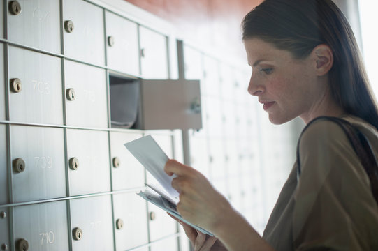 Woman taking letters from mailbox
