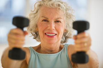 Portrait of senior woman using hand weights at gym