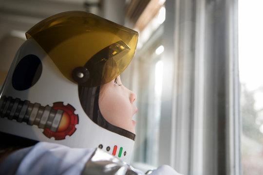 Girl wearing astronaut helmet