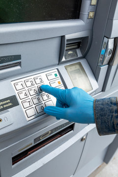 Close-up of†gloved hand on keypad of ATM machine