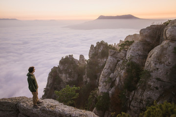 Young man standing on mountain above fog