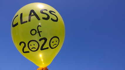 """A sad """"Class of 2020"""" balloon against a blue sky, with lots of copy space. Concept of cancelled graduation ceremonies due to Covid-19."""