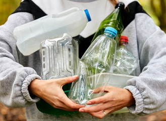 Woman holding armful of used plastic packaging and bottles