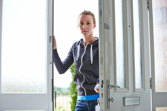 Young woman closing the front door