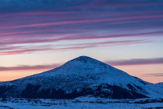 Scenic View Of Snowy Landscape Against Sky At Sunset