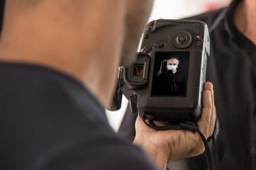 Macchina fotografica tenuta in mano che mostra lo schermino con sopra l'immagine di un uomo che indossa una mascherina chirurgica