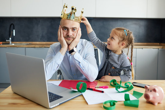 Tired Father Working from home on laptop during quarantine. Little child girl puts a toy crown on dads headon the kitchen office