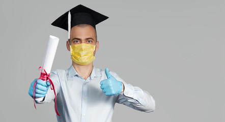 High school graduation during a quarantine. Student graduate in a hat and a protective mask holds a diploma and shows thumb up