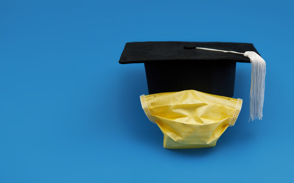 Graduation cap and face shield on blue isolated background