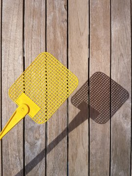 High Angle View Of Yellow Fly Swatter Over Wooden Table