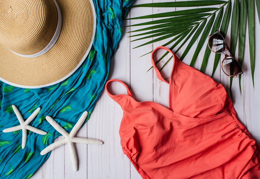 Top view of swimsuit and beach accessories on white wood background.