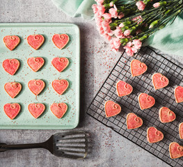 Top view of Valentine's day heart cookies cooling on pan and rack.