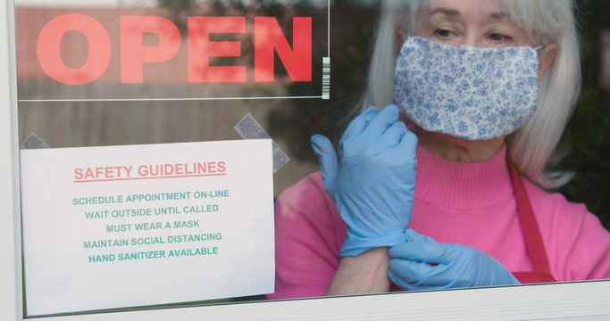 With cautious optimism a mature small business owner wearing a face mask and disposable gloves posts safety rules as she reopens her store after the coronavirus shutdown.