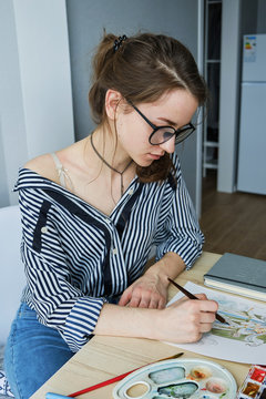 millennial girl draws fabulous images on paper while sitting at home