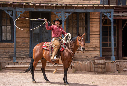 Cowboy using lasso while riding his horse through an old western town