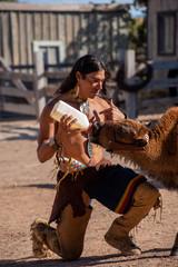 Native American man feeding baby buffalo