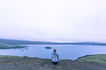 Woman sitting taking photograph of lake in highlands Iceland at sunset