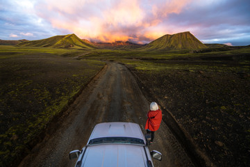 Photographer taking picture of sunset on mountains next to car Wall mural
