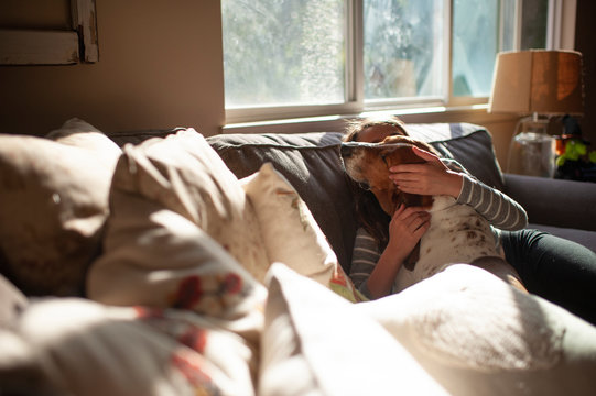 Girl hugging and kissing her dog on couch at home in pretty light