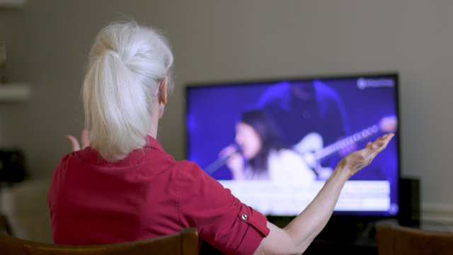 An older woman worshiping as she attends church virtually by streaming the online platform to her television because congregation and group fellowship is restricted during COVID19 pandemic.