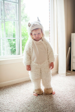 Boy dressed in llama costume making a grumpy face standing by window