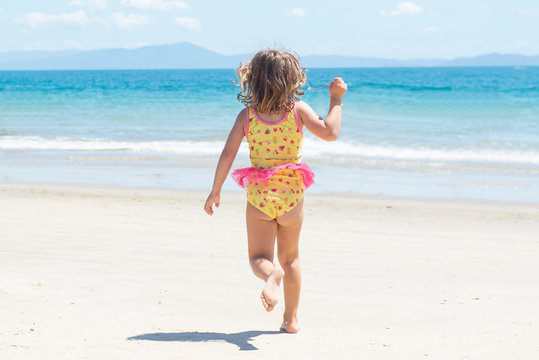 Back view of girl running in swimsuit on the beach towards the blue sea on beautiful sunny day.