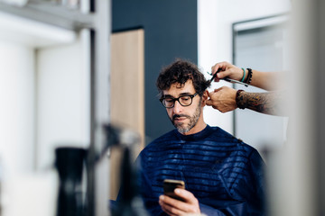 Middle aged man using phone visiting barber